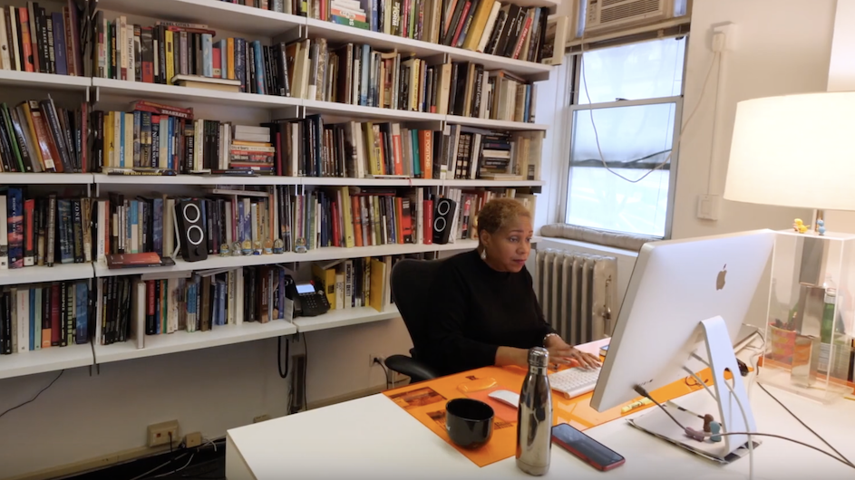 Woman sitting at her desk on her computer with shelves of books behind her