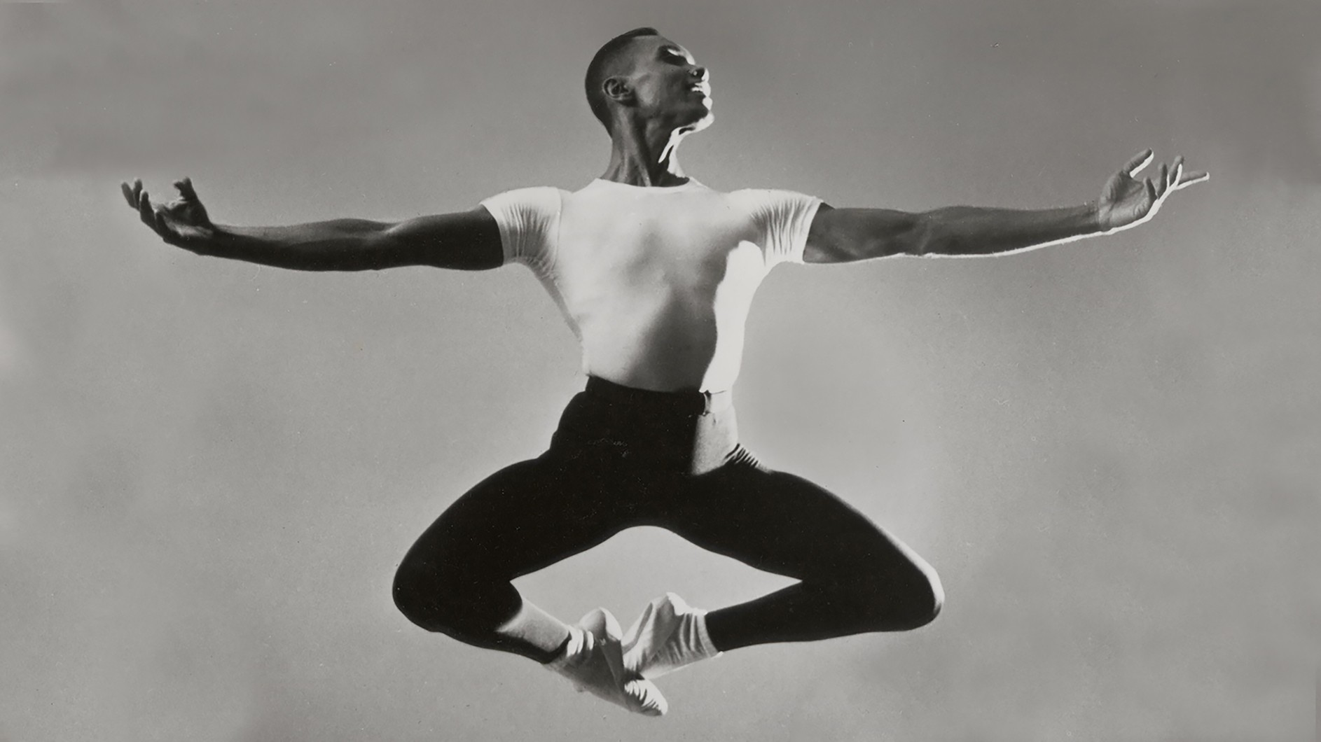 Black and white photo of man dancing - leaping in air