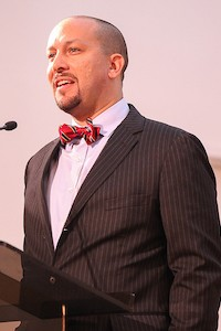 Man speaking at a podium wearing a suit with a bowtie